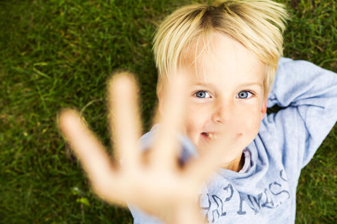 Directly above shot of happy boy gesturing while lying on grass - ASTF04407