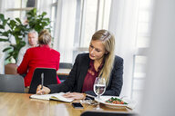 Businesswoman writing in book at table in restaurant - ASTF04628