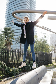 Young woman balancing and jumping on a city bench - JRFF02676
