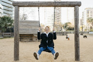 Portrait of happy young woman on a swing on playground - JRFF02679