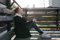 Young woman resting outdoors holding cell phone - JRFF02682