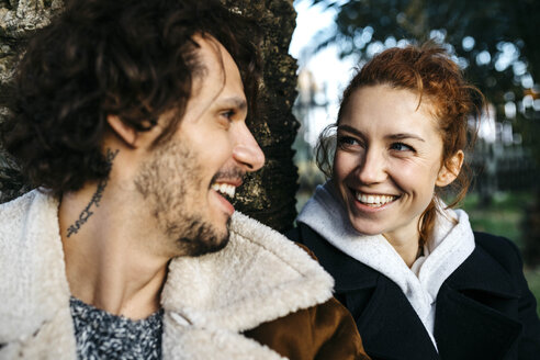 Portrait of happy couple at a tree trunk in park - JRFF02712