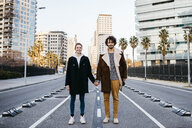 Portrait of couple holding hands in the middle of the street - JRFF02715
