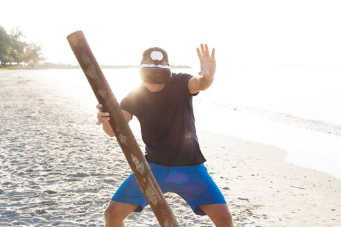 Man with wood pole wearing VR glasses on the beach - HMEF00219