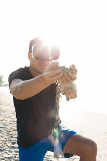 Man wearing VR glasses on the beach trickling sand through his hands - HMEF00222