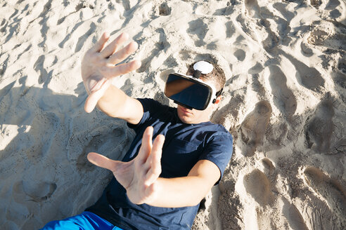 Man wearing VR glasses lying in sand on the beach - HMEF00225