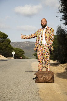 Hitchhiking man wearing suit with colourful polka-dots standing at roadside with travelling bag - KBF00510