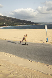 Spain, Tarifa, man wearing colourful suit skateboarding on road - KBF00513
