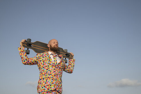 Bearded man with longboard on his shoulders wearing suit with colourful polka-dots - KBF00516