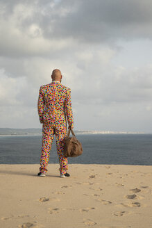 Back view of man with travelling bag wearing suit with colourful polka-dots standing on sand dune - KBF00519