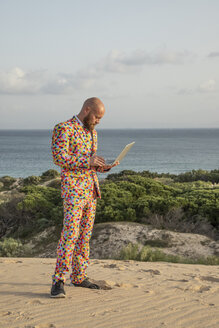 Man wearing suit with colourful polka-dots using laptop outdoors - KBF00522