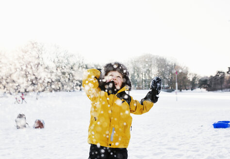 Happy boy in warm clothing enjoying snowfall - ASTF04692