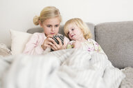 Girls using mobile phone while relaxing on sofa at home - ASTF04722