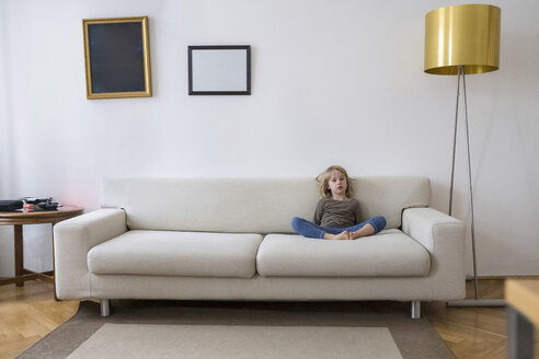Bored girl sitting on the couch at home - PSIF00243