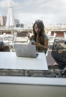 Businesswoman sitting at pavement cafe with her Chihuahua puppy using smartphone - MGOF03948