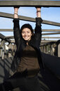 Portrait of smiling young woman on a bridge - IGGF00808