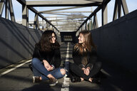 Two friends sitting on a bridge looking at each other - IGGF00811