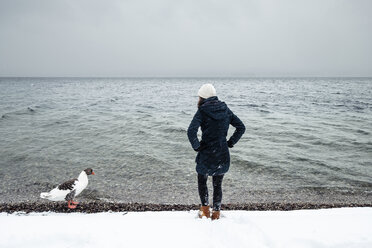 Grey goose and young woman at Lake Starnberg in winter - WFF00009