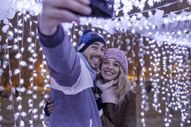 Happy young couple in winter decoration taking a selfie - ZEDF01880
