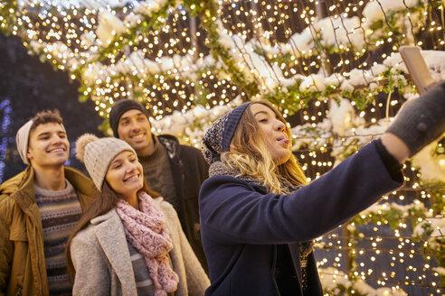 Happy friends in winter decoration taking a selfie - ZEDF01883