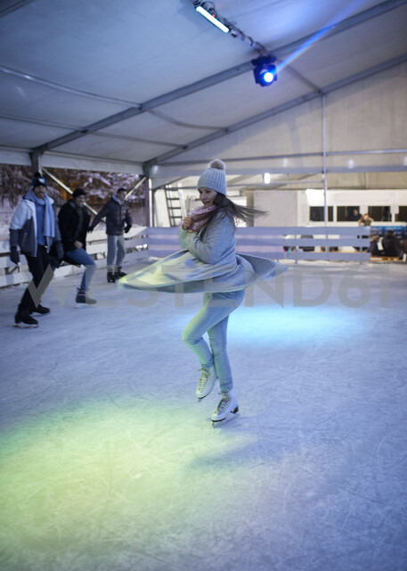 Young woman doing a pirouette on an ice rink at night watched by her friends - ZEDF01889