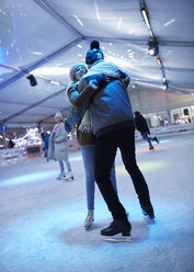 Happy young couple hugging on an ice rink at night - ZEDF01892