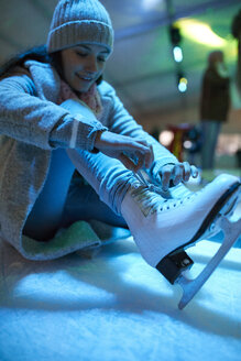 Woman sitting on ice rink putting on ice skates - ZEDF01898