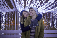 Happy young couple hugging in winter decoration - ZEDF01904