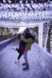 Happy young couple hugging on an ice rink at night - ZEDF01913