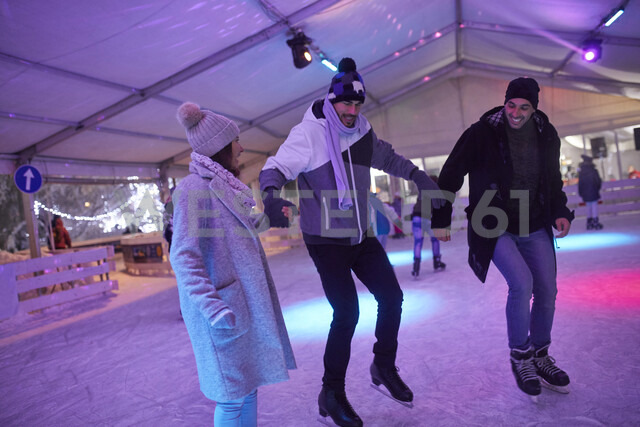 Happy friends ice skating on an ice rink at night - ZEDF01922 - Zeljko Dangubic/Westend61