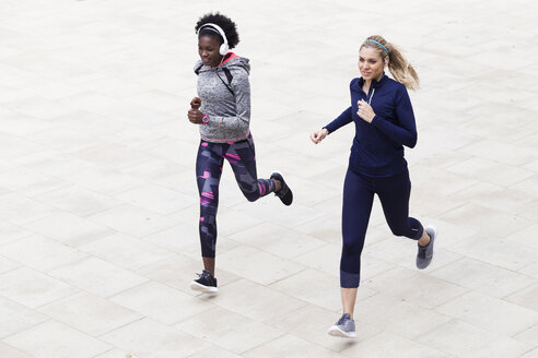 Two sporty young women running together in the city - JSRF00118