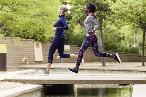 Two sporty young women running together in a park - JSRF00127