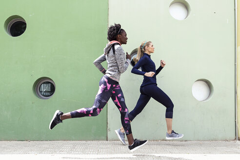 Two sporty young women running together in the city passing wall with round windows - JSRF00139