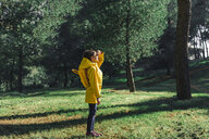 Girl wearing yellow raincoat and yellow backpack standing on a meadow at sunlight - ERRF00769