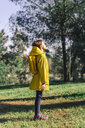 Girl wearing yellow raincoat and yellow backpack standing on a meadow enjoying sunlight - ERRF00772