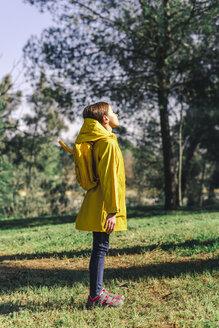 Girl wearing yellow raincoat and yellow backpack standing on a meadow enjoying sunlight - ERRF00772
