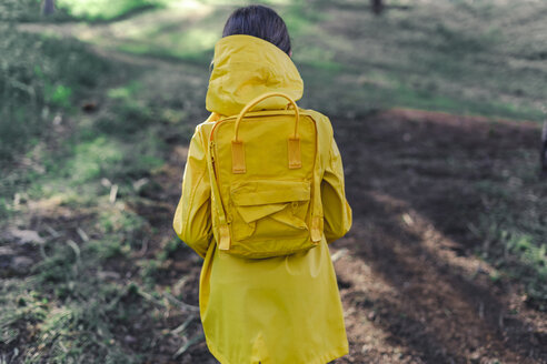 Back view of girl wearing yellow raincoat and yellow backpack in nature - ERRF00775