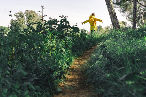 Back view of girl wearing yellow raincoat and yellow backpack in nature - ERRF00778