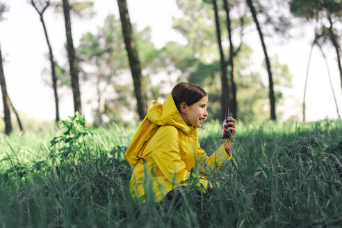 Girl with walkie-talkie wearing yellow raincoat and yellow backpack crouching on a meadow - ERRF00781
