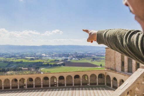 Italy, Umbria, Assisi, man's hand pointing at the fields surrounding the Basilica of San Francesco d'Assisi - FLMF00150