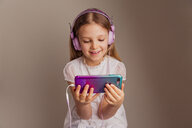 Portrait of smiling girl watching movie with smartphone and headphones - NMS00296