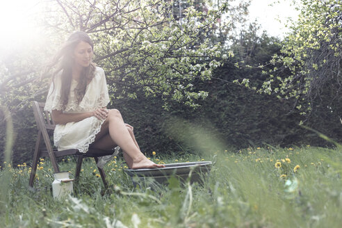 Young woman wearing white dress sittiing in garden taking footbath - WFF00013
