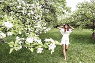 Young woman wearing white dress and floppy hat walking barefoot in garden with blossoming apple trees - WFF00019