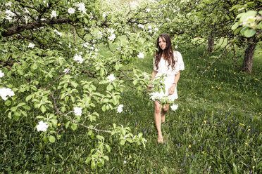 Young woman wearing white dress walking barefoot in garden with blossoming apple trees - WFF00025