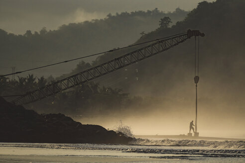Indonesia, Sumbawa Island, Man and construction crane at seaside - KNTF02684