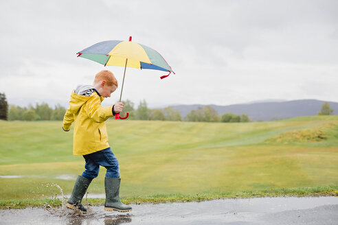 Redheaded little boy with umbrella playing in the rain - NMS00298