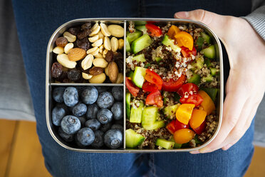 Girl holding a lunchbox with quinoa salad, blue berry and trail mix - LVF07830