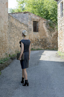 Italy, Tuscany, Monteriggioni, woman with laptop walking in the village - PSTF00295