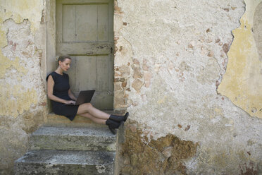 Italy, Tuscany, Monteriggioni, woman sitting at house entrance using laptop - PSTF00298