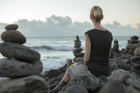 Spain, Tenerife, Costa Adeje, woman sitting between cairns at the coast - PSTF00304